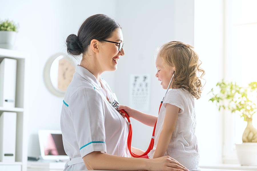 Life and Health Insurance - Young Girl Gets a Checkup, Uses the Doctor's Stethoscope on the Pediatrician for Fun