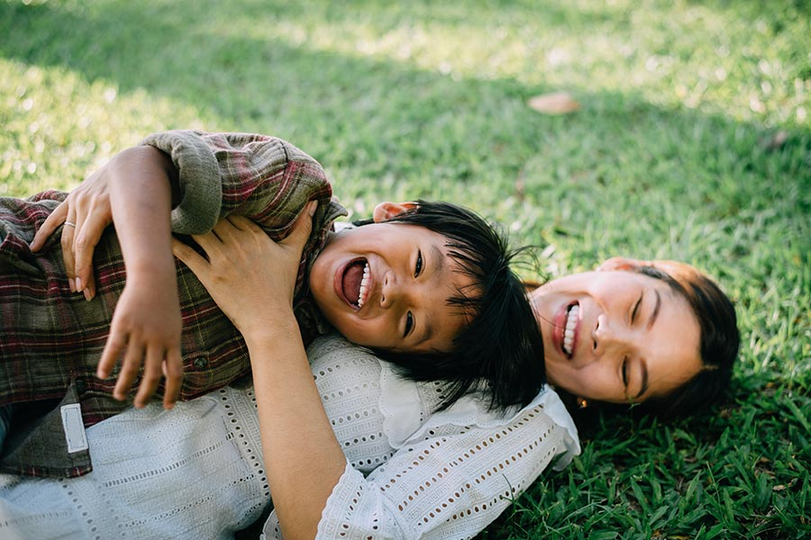 Personal Insurance - Mom and Young Son Roll Around in the Grass, Laughing and Hugging