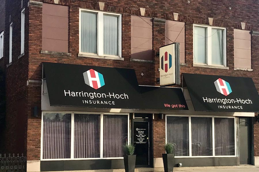 Richmond, IN Insurance - Harrington-Hoch Insurance's Richmond, Indiana Office Location, Featuring Red Brick Facade, Black Awning With Company Name, Large Windows and Potted Plants