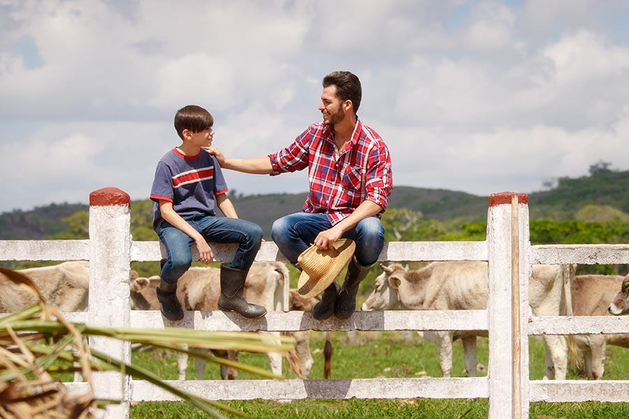 Specialized Business Insurance - Father and Son Sit on a Fence on Their Cattle Ranch, Dad Patting Son's Shoulder