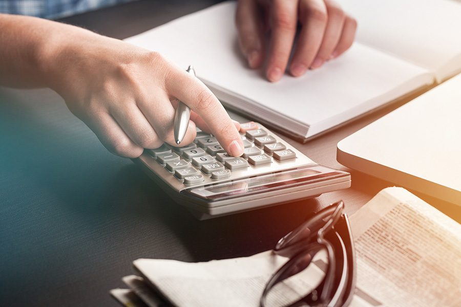 Payroll Solutions - Man Sitting at Desk Working on Business Accounting