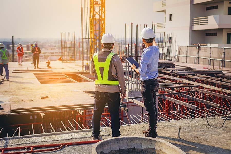 Specialized Business Insurance - Contractor and Structural Engineer Discussing New Building Construction at Jobsite